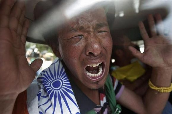 A Tibetan exile shouts slogans inside a car after being detained by police during a protest against the visit of Chinese President Hu Jintao to India, near the venue for the BRICS (Brazil, Russia, India, China and South Africa) Summit in New Delhi