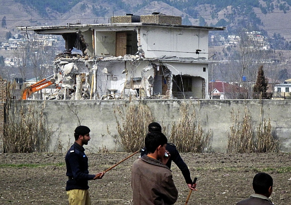 Policemen and residents stand near while demolition work is carried out on the building where bin Laden was killed by U S special forces last May, in Abbottabad