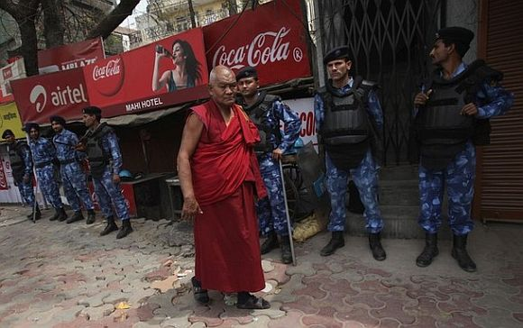 A Tibetan exile walks past Rapid Action Force (RAF) personnel at Majnu Ka Tila, a Tibetan refugee camp, in New Delhi