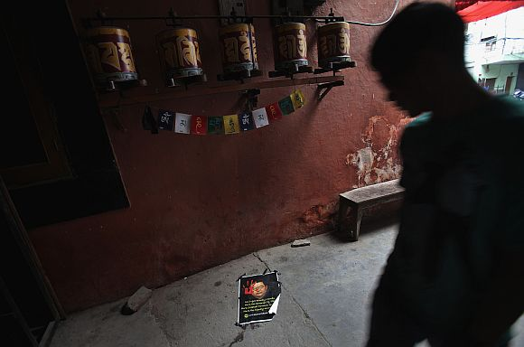 A Tibetan exile walks past a poster of Chinese President Hu Jintao at Majnu Ka Tila, a Tibetan refugee camp, in New Delhi