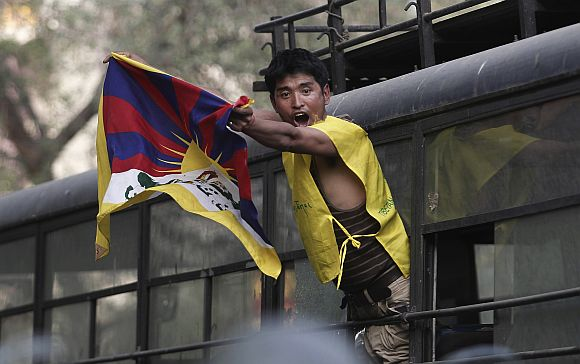 A Tibetan exile shouts slogan from a police vehicle after being detained during a protest