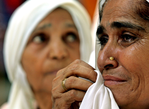 Relatives of victims of the 1984 anti-Sikh riots weep during a protest in New Delhi
