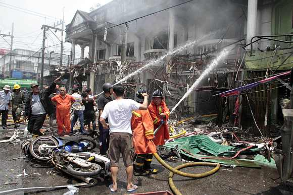 Thai rescue workers extinguish a fire at the site of a car bomb blast in southern Thailand's Yala province
