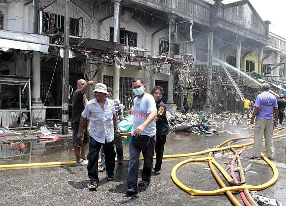 Thai rescue workers help an injured man after a bomb blast in southern Thailand's Yala province