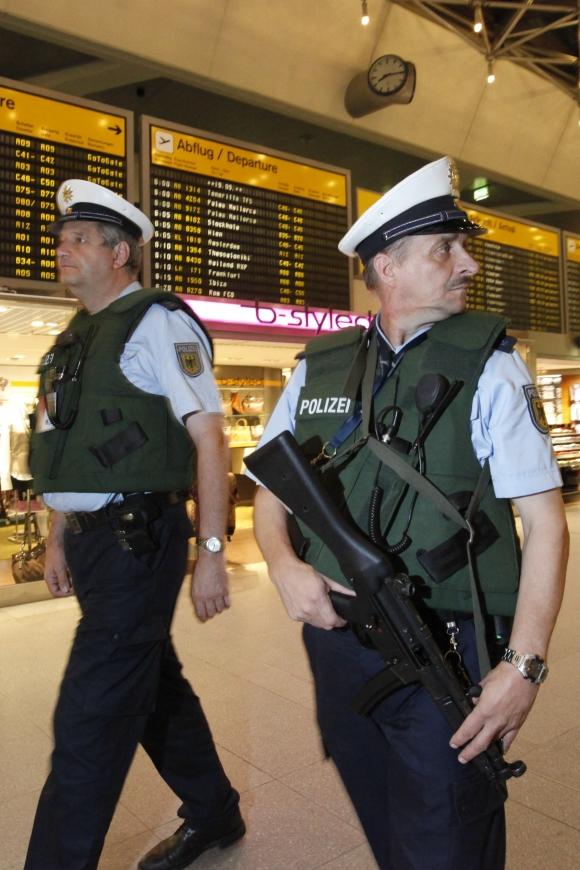 German policemen patrol with bulletproof vests and weapons at Berlin's Tegel airport