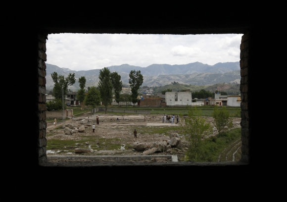 Children are seen through the window of a house under construction as they play cricket on the demolished site of a compound of Osama bin Laden in Abbottabad
