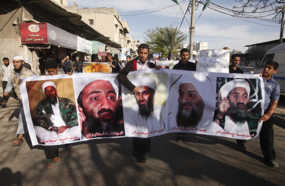 Palestinians hold pictures of Osama bin Laden during a protest against his killing