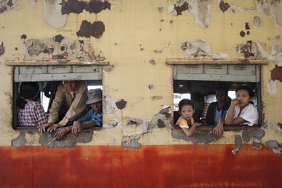 People travelling towards Yangon look through windows as the train stops at Danyingone Station.