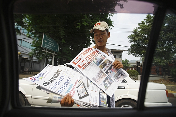 A street vendor selling weekly journals displays some journals towards a vehicle stopping at a red light in Yangon.