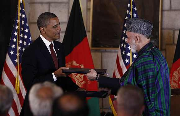Obama and Karzai exchange documents after signing the strategic partnership agreement at the Presidential Palace in Kabul