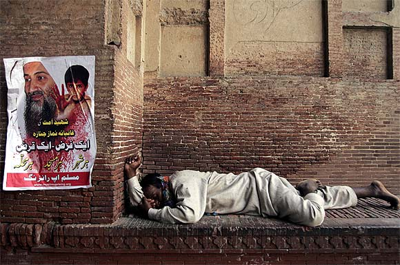 A man takes a nap next to a poster of Osama bin Laden at the Chauburji monument in Lahore