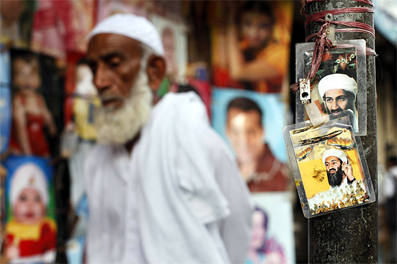 A man walks past images of Al Qaeda leader Osama bin Laden displayed near a poster shop