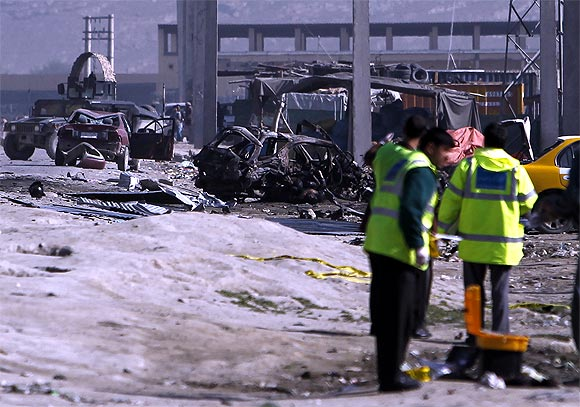 Afghan security forces members inspect the site of a car bomb attack in Kabul