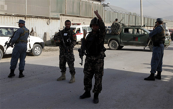 Afghan security forces members keep guard at the site of a car bomb attack