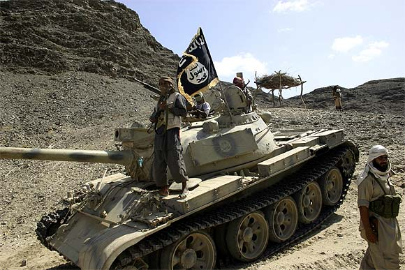 Members of Ansar al-Sharia, an Al Qaeda-affiliated group, are seen near a tank taken from the army during recent battles, as they guard a road leading to the southern Yemeni town of Jaar