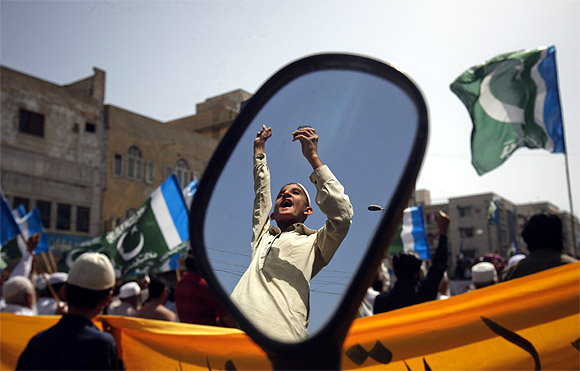 A supporter of the Jamaat-e-Islami is reflected in a mirror of a motorbike during an anti American and NATO demonstration in Karachi