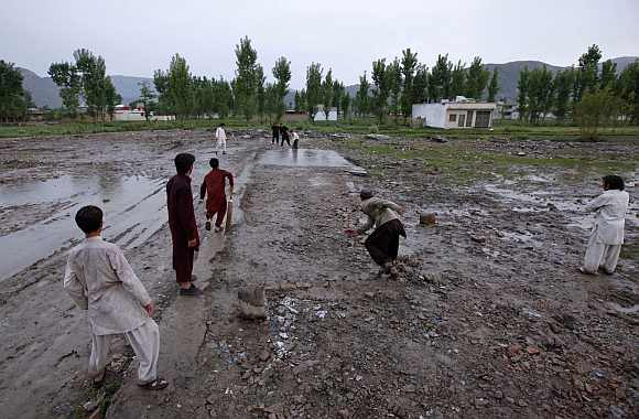 Children play cricket in the rain on the demolished site of the compound of Osama bin Laden, in Abbottabad. Osama bin Laden was killed a year ago, on May 2, 2011, by a United States special operations military unit in a raid on his compound