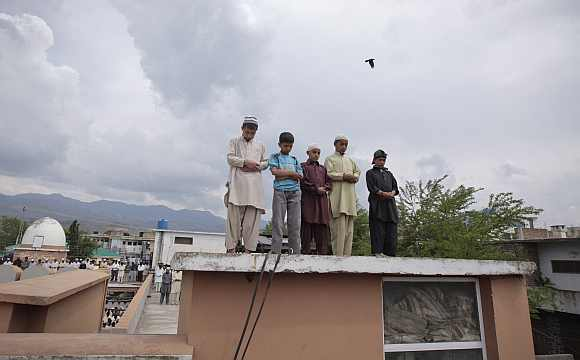 Children offer prayers on the roof of Jamia Masjid Mandian in Abbottabad
