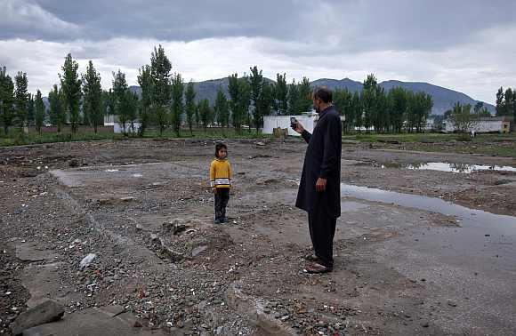 Six-year-old Anum, poses for her uncle for a picture while visiting the site of the demolished compound of Osama bin Laden