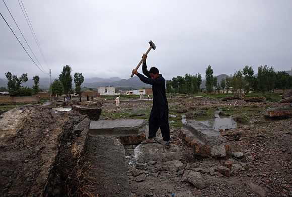 A boy uses a hammer to break a concrete block to scavenge for iron from the demolished compound in Abbottabad
