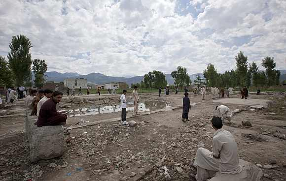 Residents sit near children playing cricket on the demolished site of a compound of Osama bin Laden