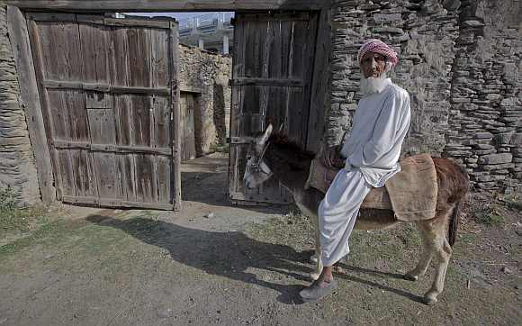 An elderly man rides a donkey along a road in the outskirt of Abbottabad