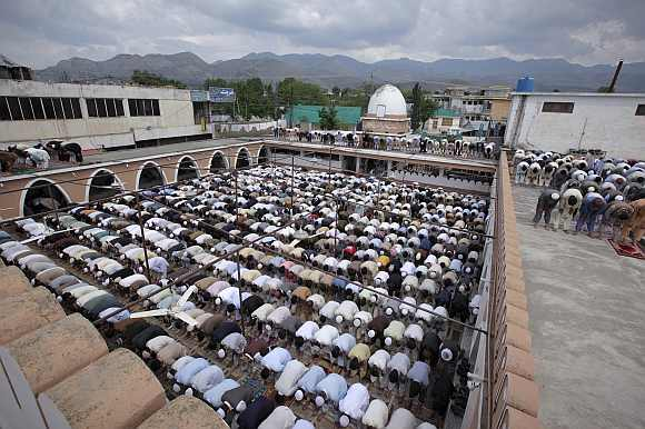 Residents offer prayers in an open yard of the Jamia Masjid Mandian in Abbottabad