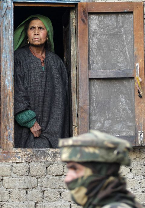 A Kashmiri woman looks out from the window of her house as an Indian soldier keeps guard during a gun battle between security forces and terrorists in the village of Dadsar, 37 km south of Srinagar