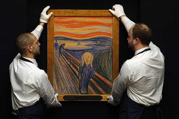 Sotheby's employees pose for a photograph with Edvard Munch's 'The Scream' at Sotheby's auction house in London