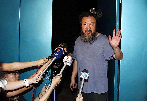 Dissident Chinese artist Ai Weiwei waves from the entrance of his studio after being released on bail in Beijing June 23, 2011