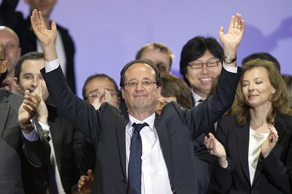 France's newly-elected President Francois Hollande celebrates on stage with his companion Valerie Trierweiler and Socialist party members during a victory rally at Place de la Bastille in Paris early May 7