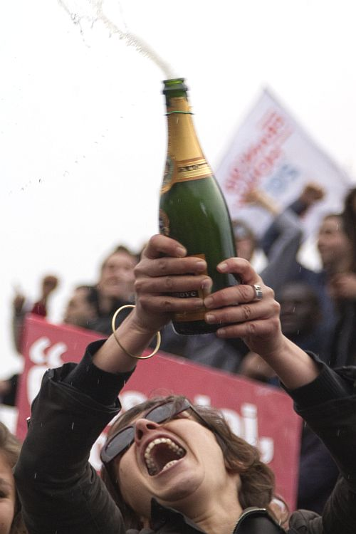 A supporter of Francois Hollande, Socialist Party candidate for the 2012 French presidential election, celebrates with champagne during a rally at Place de la Bastille in Paris