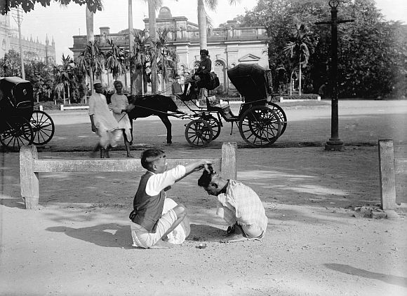 A hairdresser giving a 'Hindustani haircut' (pudding bowl), on Strand Road South, Kolkata. The High Court is in the left distance, the building behin
