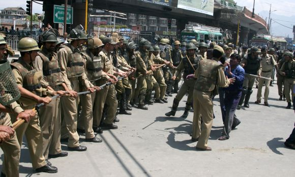 A striking protestor clashes with police in Srinagar on Wednesday