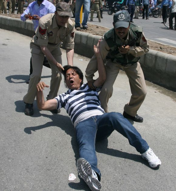 A protesting J&K government employee is removed by the security personnel in Srinagar as their strike reached second day on Wednesday