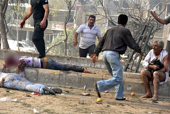 People run to help those wounded at the site of an explosion in Damascus