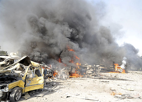 Smoke rises from the wreckage of mangled vehicles at the site