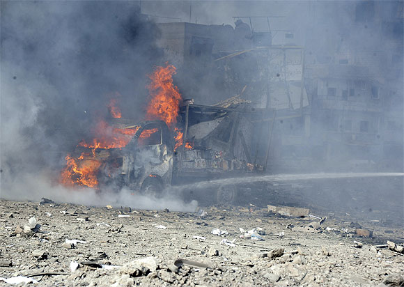A vehicle burns at the site of an explosion in Damascus