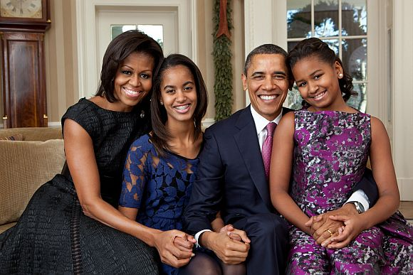 President Barack Obama, First Lady Michelle Obama, and their daughters, Malia, left, and Sasha, right, sit for a family portrait in the Oval Office