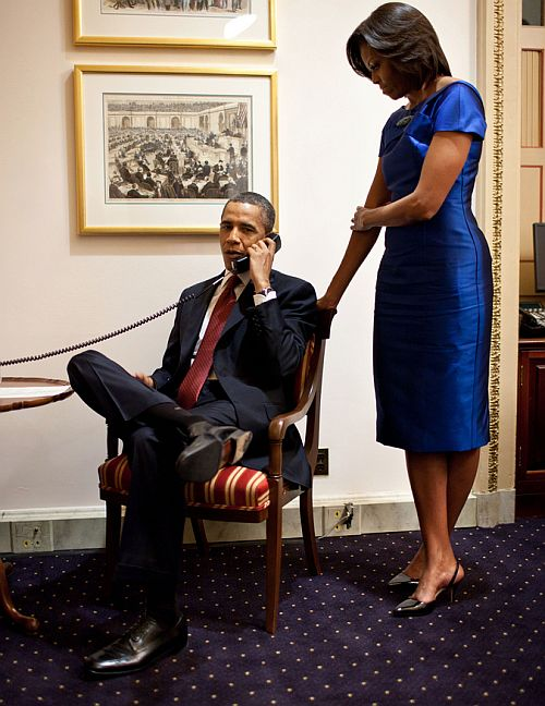 First Lady Michelle Obama stands behind the President as he makes a phone call
