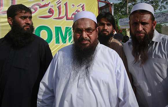 Hafiz Saeed, the head of Jamaat-ud-Dawa, gestures to the media as he arrives to attend a rally organised by the Defence Council of Pakistan in Lahore