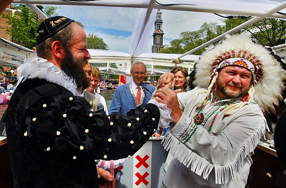 Scott Brown, dressed as a native American puts the ring on the finger of Dutch born Pilo Pilkes, dressed as Henry Hudson (left) after being married by Amsterdam's Mayor Job Cohen (centre) on an official wedding boat during the Gay Pride Canal Parade in Amsterdam