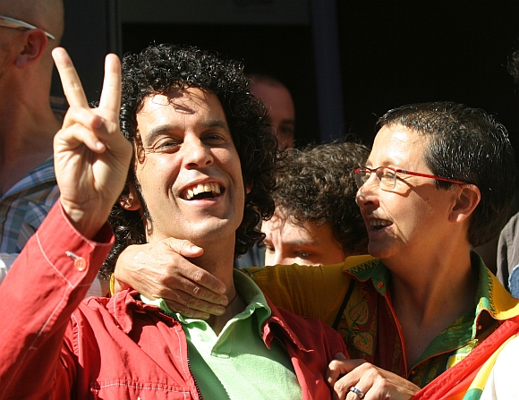 Gay rights activist and member of the Spanish Socialist Workers' Party executive board Pedro Zerolo (left) flashes a victory sign outside Madrid's parliament