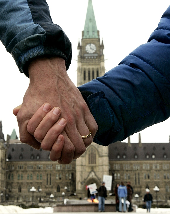 A married couple hold hands in front of the Canadian Parliamentary building in Ottawa