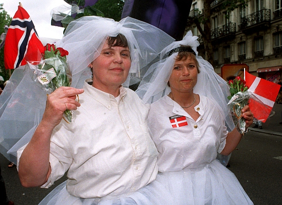 A Norwegian and Danish lesbian couple is dressed up as brides during a march with tens of thousands of homosexuals from all over Europe in their Europride festive parade  in Oslo
