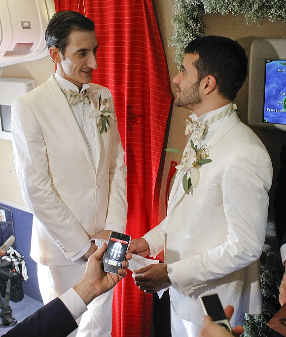 Aleksander Mijatovic (left) and his partner Shantu Bhattacharjee exchange personal vows after they were married at a civil wedding ceremony onboard a Scandinavian Airlines flight from Stockholm to Newark