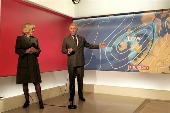Prince Charles is watched by his wife Camilla as he presents a special weather forecast