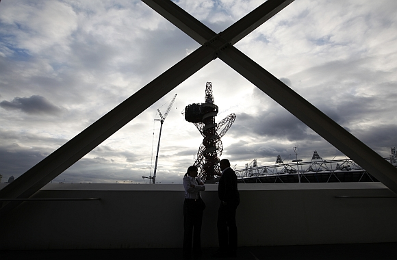 A couple share a moment at the Olympic Aquatics Centre, as Anish Kapoor's ArcelorMittal Orbit tower and the Olympic stadium are seen in the background, at the Olympic Park in London