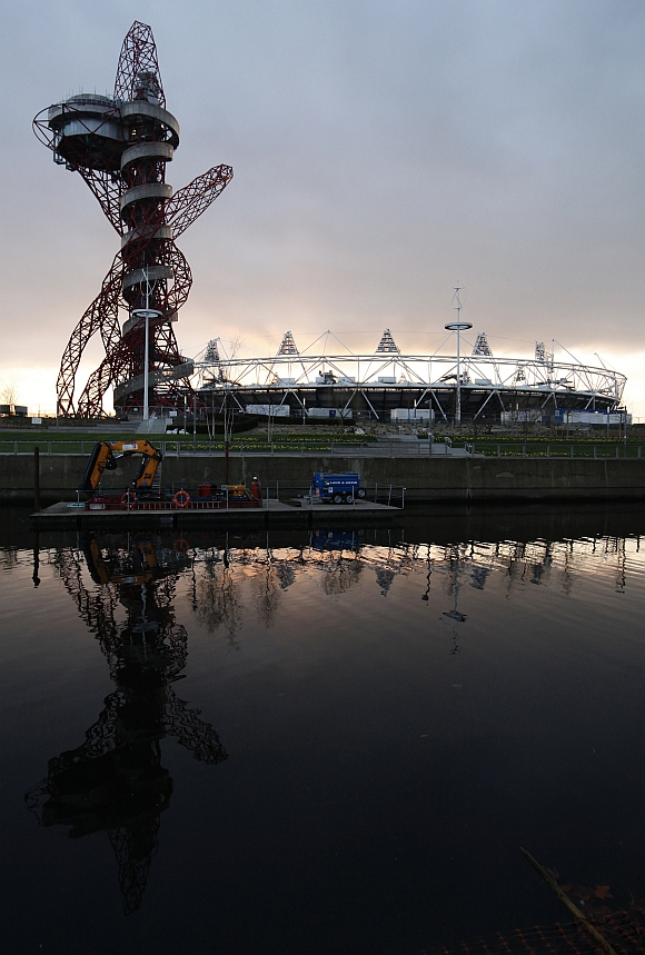 The Olympic stadium and Anish Kapoor's ArcelorMittal Orbit tower are reflected in a canal in Stratford, east London