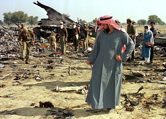 A relative of a Saudi Arabian victim of the mid-air collision, walks through wreckage of the Saudi Arabian jumbo jet outside the village of Charkhi Dadri